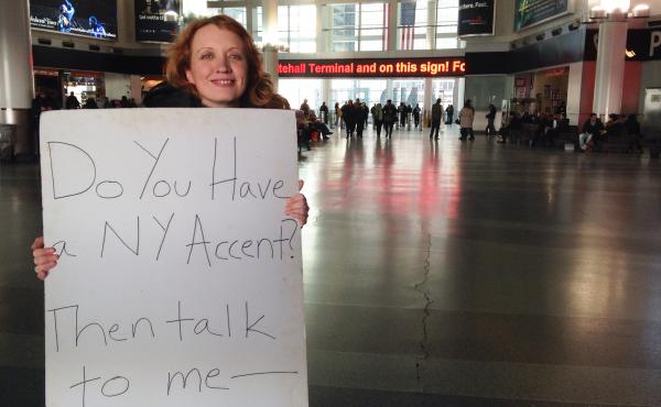 Heather Quinlan searched for New York accents around the city for her documentary If These Knishes Could Talk. She holds up a sign at the Whitehall Ferry Terminal in Manhattan.