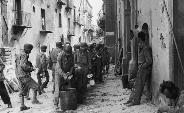 American GIs line up in the street in Troina, Sicily, utensils and dishes in hand, as they wait for a meal from a large pot, July 1943. Oregano grows abundantly in Southern Italy, where many GIs encountered the herb for the first time, and fell in love. M