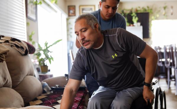 Joel Ramirez climbs back into his wheelchair with the help of Francisco Guardado, a home health aide, at his home in Rialto, Calif. Ramirez was paralyzed from the waist down in 2009 when a 900-pound crate fell on him at a warehouse. Changes to California