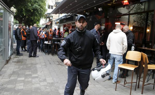 An Israeli policeman runs at the scene of a shooting incident in Tel Aviv, Israel on Friday.