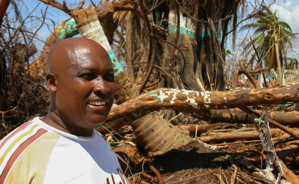 Nicholas Buisson stands next to his tattered hammock on the beach in front of his house in Port Salut.
