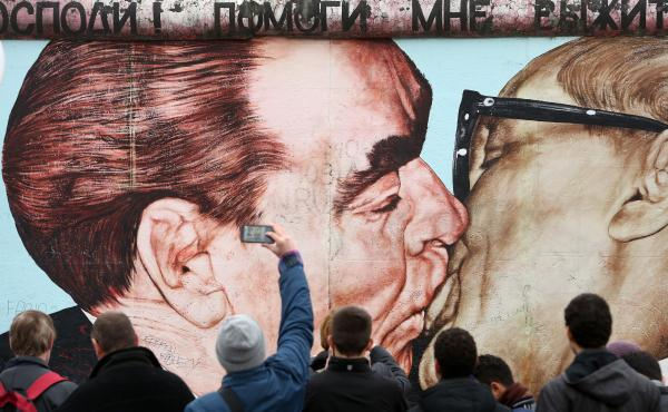 "Dmitri Vrubel's painting of the Soviet Union's Leonid Brezhnev and East Germany's Erich Honecker kissing — under a Russian phrase that reads, ""My God, Help Me to Survive This Deadly Love"" — is a popular part of the East Side Gallery."
