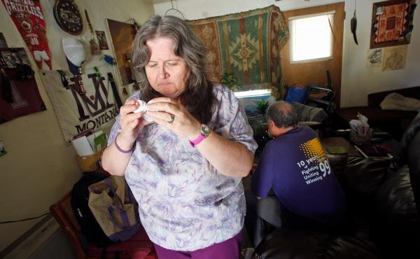 Celeste Thompson, 57, a home care worker in Missoula, Mont., examines a pill bottle in her home. Thompson cares for her husband, and worries that if she loses her Medicaid coverage she won't be able to afford to see a doctor.