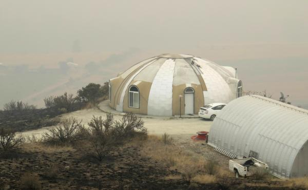 John Belles' concrete dome house outside Omak, Wash., has survived the wildfires unscathed amid acres of blackened hillside. The fires have caused air quality in the area to be deemed hazardous by the Washington State Department of Ecology.