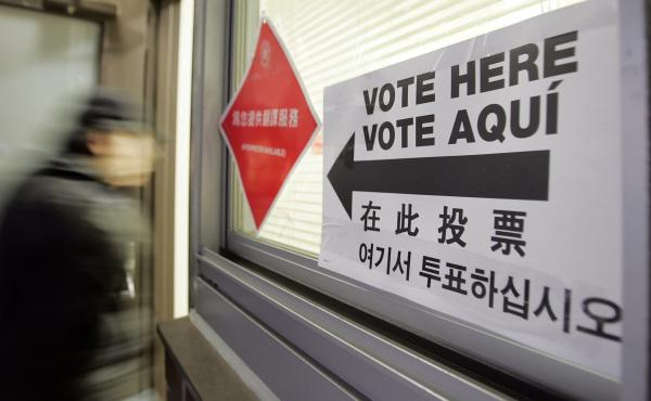 A voter enters a polling place with multilingual instructions in New York City's Chinatown in 2006. Analysts have described the Asian-American political shift as one of the most dramatic swings in recent presidential voting behavior across any demographic