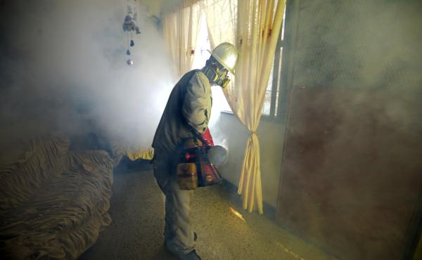 A Health Ministry employee fumigates against Aedes Aegypti mosquito, which can carry the Zika virus, at a home in Caracas on January 28.