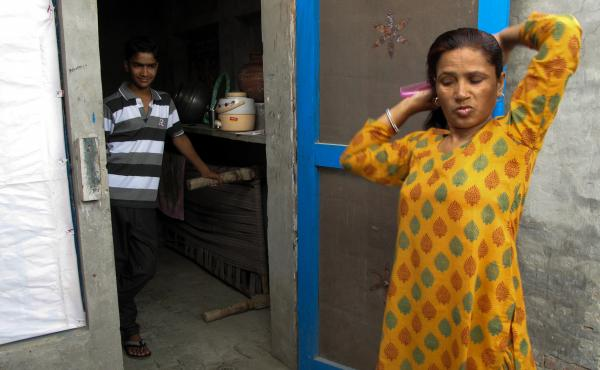 Saroj's teenage son watches her comb her hair before she heads to work.