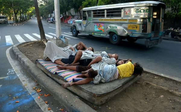 Street children sleep on a discarded mattress on a center island near a road crossing in Manila, Philippines, in April. After 15 years of the Millennium Development Goals, Asia as a region has had the fastest progress, reports the U.N., yet hundreds of mi