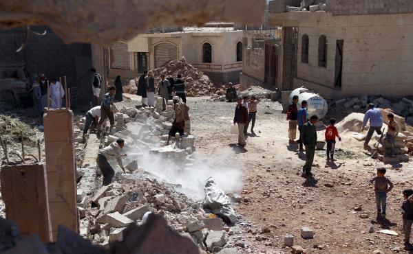 Yemeni men clear debris following an airstrike by the Saudi-led coalition in the capital, Sanaa, on Nov. 29.