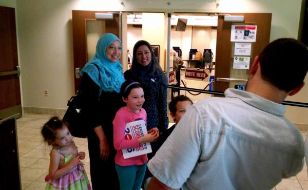 Alana Raybon, in a blue head scarf, pauses for a photo with a friend and her children after voting in Nashville's Howard Office Building.