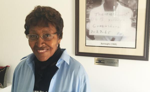 """Theresa Burroughs, 80, stands by a photograph of her as a young woman getting arrested for trying to register to vote. The right is sacred to her today.    """"Every time there's a vote, I go,"""" she said."""