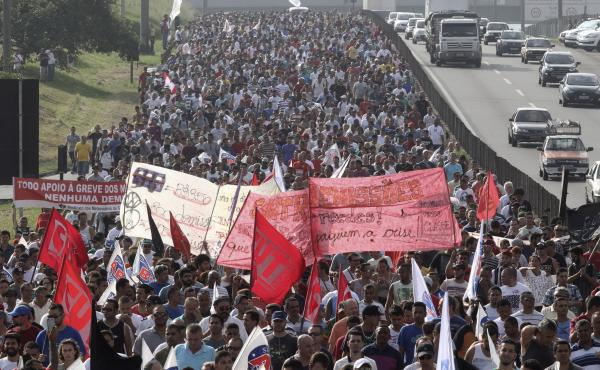 Mercedes-Benz, Ford and Volkswagen workers block the Anchieta highway in Sao Bernardo do Campo. Thousands of metalworkers marched to protest layoffs by carmakers expecting little or no rebound from a sharp 2014 downturn.