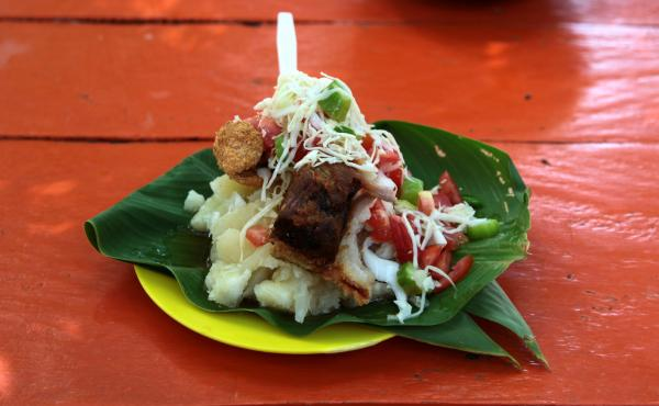 Vigorón served at El Gordito in Granada, Nicaragua. The combination of soft, starchy yucca; salty, rough pork cracklings; and tangy, cool slaw made with cabbage, onions, tomato, mimbre fruit (also known as mimbro), chile and vinegar offers a distinct int