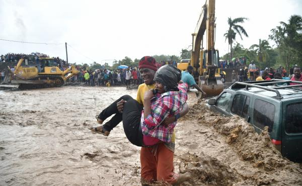 People help each other across the river La Digue in Petit Goave, Haiti, on Wednesday, a day after Hurricane Matthew raked the island nation.