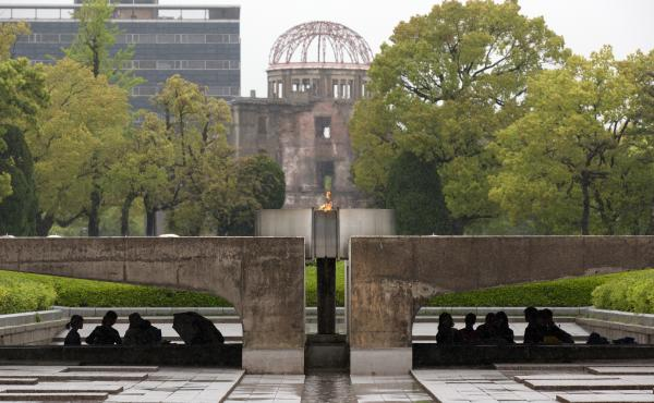 Visitors shelter from the rain under the Peace Flame as they visit the Memorial Park and the nearby Hiroshima Peace Memorial Museum on April 21 in Hiroshima, Japan. The dome in the background was destroyed during the attack, and preserved as a monument. T
