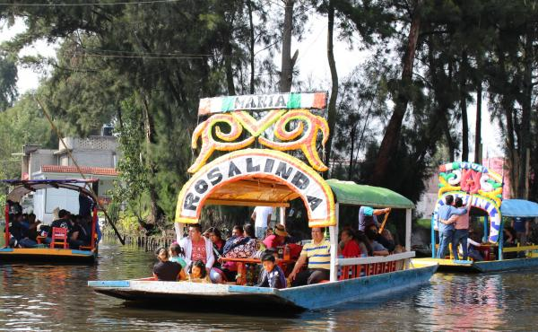 A trajinera called Rosalinda carries a family along the Xochimilco canals in Mexico city. The borough and its canals are a UNESCO World Heritage Site.