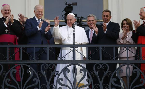 Pope Francis waves to a crowd from the speaker's balcony at the Capitol on Thursday. In his speech, Francis lauded two Catholics: Dorothy Day and Thomas Merton.