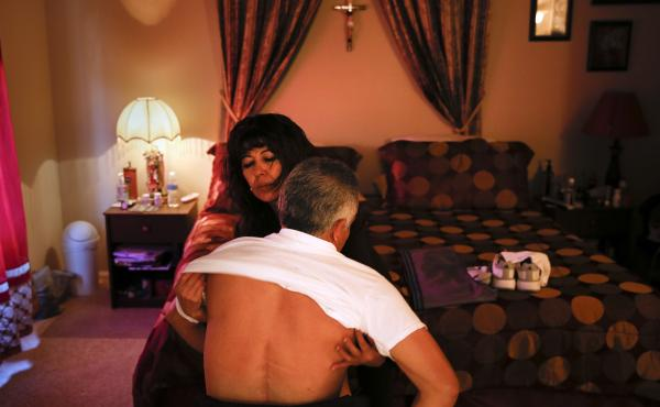 Lupita Ramirez dresses her husband, Joel, at their home in Rialto, Calif. Joel was paralyzed from the waist down after being crushed by a pallet when he was working in a warehouse.