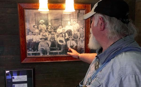 Tour guide Ron Craig points to a photo in Jack Daniel's old office at the whiskey maker's distillery in Lynchburg, Tenn. The photo, taken in the 1890s, shows Jack Daniel (wearing a black-banded white hat and a gray goatee), seated next to an African-Ameri