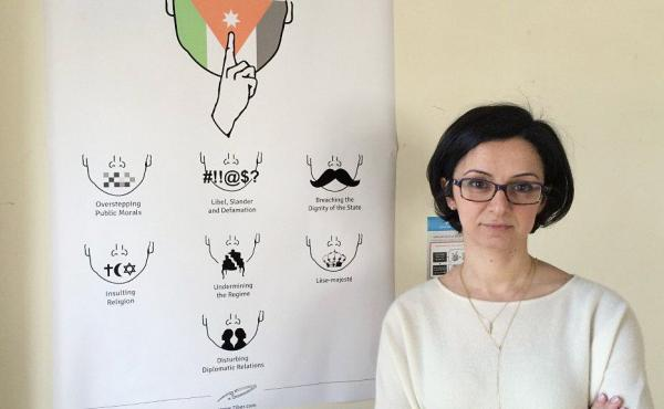 Lina Ejeilat helped found the Jordanian online magazine 7iber (pronounced 'Hebber'). While the government encourages free expression in principle, many strict regulations remain, as noted by the satirical chart next to her.