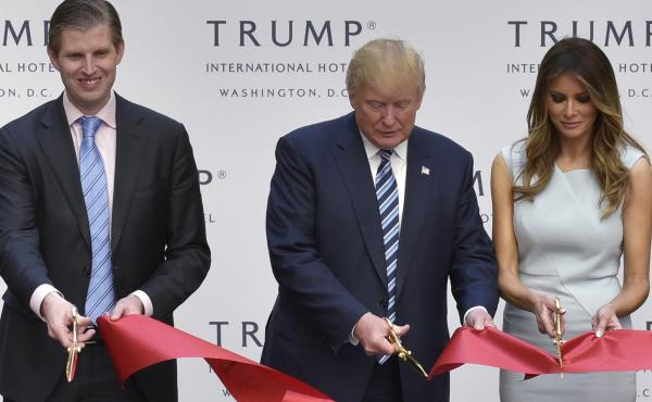 Donald Trump, along with his wife, Melania, and son Eric, cuts the ribbon during the grand opening ceremony for the Trump International Hotel, located in the Old Post Office building in Washington, D.C. The building, which is owned by the General Services