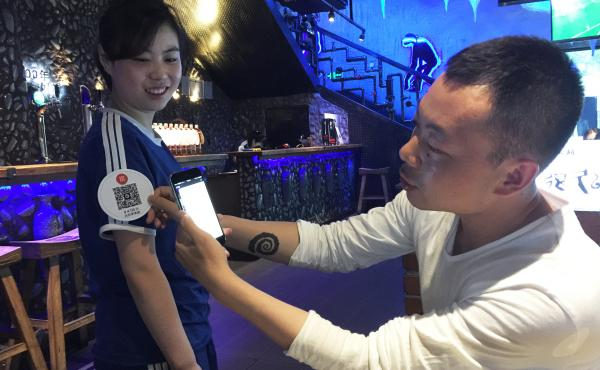Beijing-based restaurateur Song Ji (right) demonstrates his system, which allows customers to tip waitstaff. Diners use smartphones to scan QR codes that the waitstaff wear on their sleeves. This generates a tip of 4.56 yuan, or about 70 cents. Waitress L