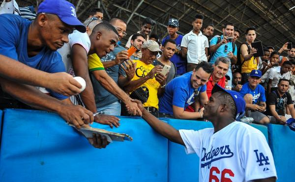 Los Angeles Dodgers star Yasiel Puig shakes hands with fans Dec. 16 at the Latin American Stadium in Havana during a Major League Baseball goodwill tour. Puig and fellow Cuban national Jose Abreu of the Chicago White Sox returned home Tuesday for the firs