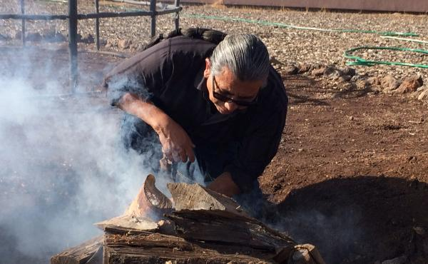 Shannon Rivers, a member of the Akimel O'odham tribe, lights a fire for the purification ceremony at the Coconino County jail. Inmates will help him put blankets over the sweat lodge structure, place heated rocks inside and pour water over them.