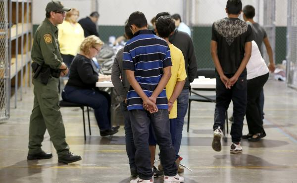 Boys wait in line to make a phone call at the U.S. Customs and Border Protection Nogales Placement Center in Arizona in June. Many of the minors who arrived from Central America last year are now awaiting court hearings to determine if they can stay in th