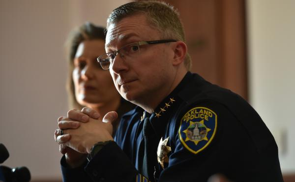 Oakland Police Chief Sean Whent, with Mayor Libby Schaaf behind him, listens to questions from the media  on May 2, 2015, after May Day protests in Oakland, Calif. Whent has since resigned as police chief — as did two interim chiefs after him, over the