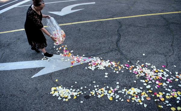 A woman places flower petals along the entrance to Cave Hill Cemetery for the funeral procession.