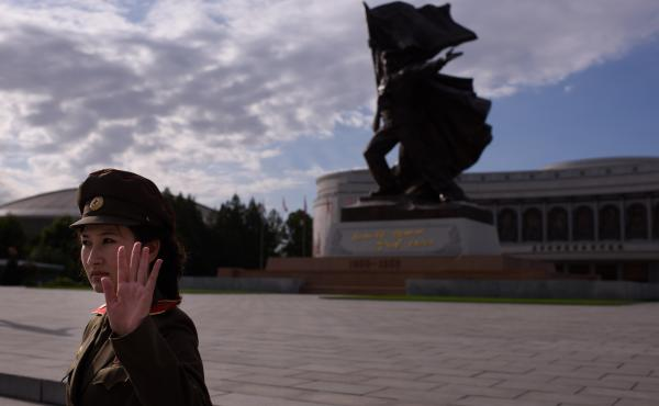 A uniformed tour guide gestures to tourists outside the War Museum in Pyongyang. U.S. citizens can visit North Korea as tourists.