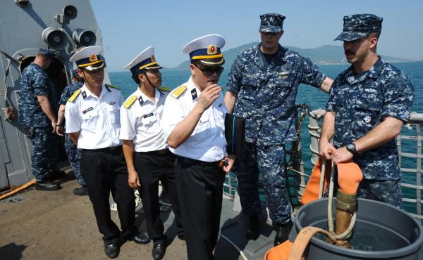 Vietnamese navy officers (in white) talk with U.S. sailors aboard the guided missile destroyer USS Chafee in the central Vietnamese city of Danang in 2012. The two countries have increased military cooperation in recent years and President Obama announced