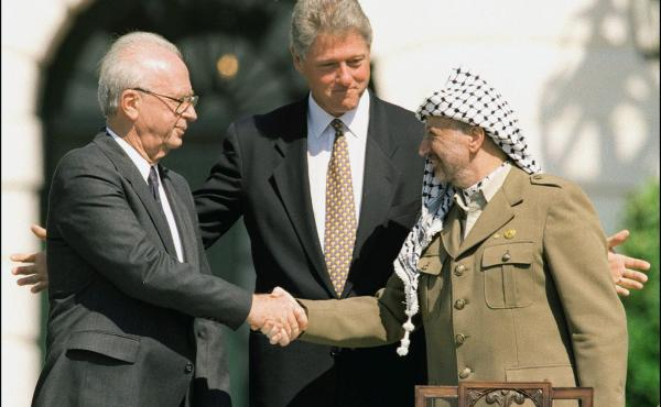 Israeli Prime Minister Yitzhak Rabin (left) and Palestine Liberation Organization Chairman Yasser Arafat (right) shake hands at the White House in front of President Bill Clinton in September 1993. The new play OSLO is a dramatization of the events that l