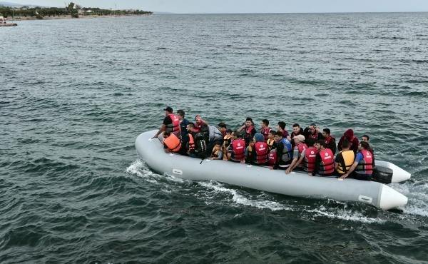 Migrants on a dinghy head to the Greek island of Lesvos last Thursday. Some 48,000 migrants have landed on Greek shores so far this year, with about half coming to Lesvos, a popular vacation spot for European tourists. Some islanders and tourists are assi