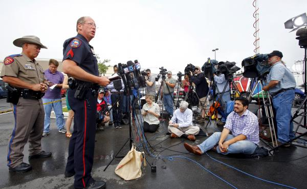 Sgt. Patrick Swanton of the Waco Police Department speaks to the media as Texas Department of Public Safety Trooper D.L. Wilson (left) stands near a Twin Peaks restaurant where nine members of a motorcycle gang were shot and killed in Waco, Texas, on Tues