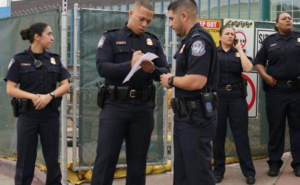 Customs and Border Protection agents stand at the San Ysidro Port of Entry on Friday, Feb. 10. One memorandum issued by the Department of Homeland Security says the government will hire new ICE officers and Border Patrol agents, but it doesn't mention hir