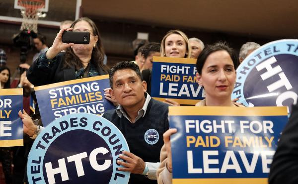 Supporters watch as New York Gov. Andrew Cuomo speaks to promote his paid family leave initiative at a rally in Manhattan on March 10.