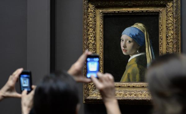 """Vermeer's Girl with a Pearl Earring stares back at cellphones at the Frick Collection in New York City. """"The art museum used to offer objects, works of art, the finest that we have,"""" Lewis says. """"And it's gone from offering objects to offering an experien"""