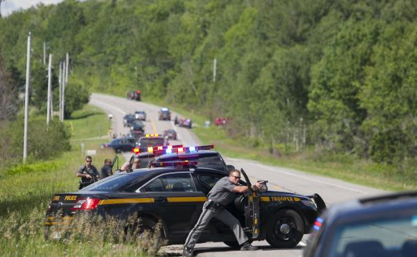 Law enforcement personnel take cover Friday afternoon after cornering two escaped prisoners off of Route 30 in Malone, N.Y. One prisoner, Richard Matt, was shot dead by law enforcement. Authorities were still searching for escapee David Sweat late Friday