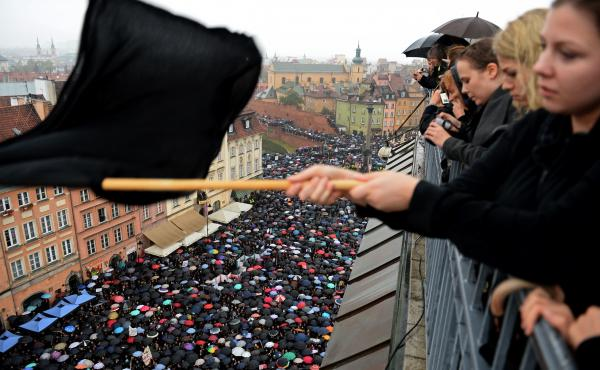A demonstrator waves a black flag on Monday as people in Warsaw take part in a nationwide strike and demonstration to protest against a legislative proposal for a total ban of abortion in Poland.