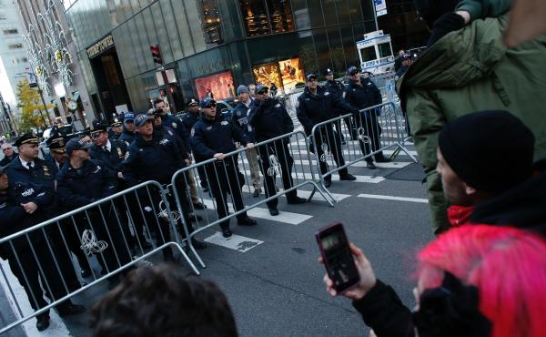 New York police officers block the street during a protest against U.S. President-elect Donald Trump in front of Trump Tower on Nov. 12, 2016 in New York. Americans spilled into the streets Saturday for a new day of protests against Trump, even as he appe