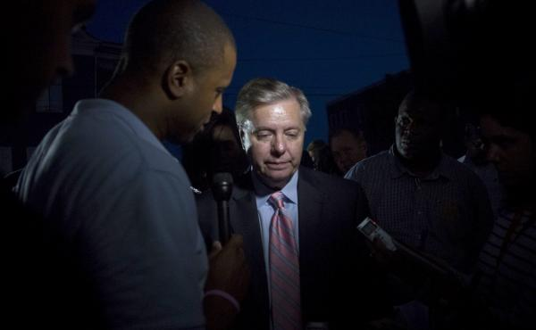 Sen. Lindsey Graham, R-S.C., speaks to members of the media after visiting the memorial site at the Emanuel African Methodist Episcopal Church in Charleston, S.C., where nine people were killed.