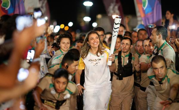 The Olympic flame gets a lift from former Brazilian volleyball player Leila Barros, who took part in this month's torch relay. The games are set to begin on Aug. 5.