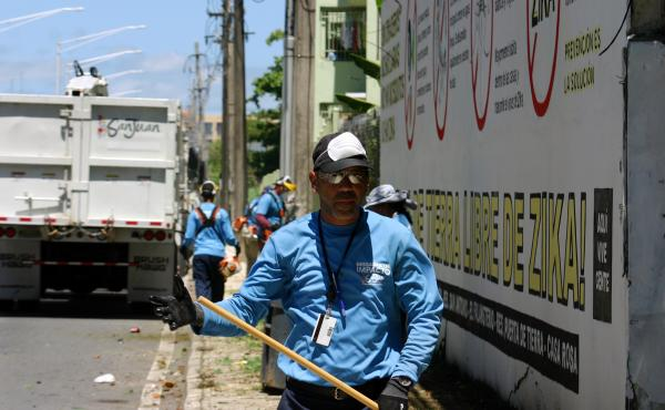 A city worker in San Juan, Puerto Rico, cleans up a vacant lot where mosquitoes could be breeding.