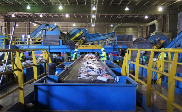 Workers pull out plastic and trash from a conveyor belt of paper at a recycling plant in Elkridge, Md. The plant processes 1,000 tons of recyclable materials every day.