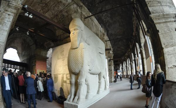 """People walk past a replica of an ancient statue of a human-headed winged bull from Nimrud, Iraq, destroyed by the Islamic State. It's part of an exhibition called """"Rising from Destruction"""" at Rome's Colosseum."""