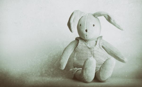 A cute, stuffed children's bunny rabbit toy wearing a striped onesie sitting down against a plain background. Vintage photo style (wet place, monochrome) image with great copy space.