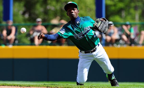 """Joshua Muwanguzi of Uganda's team throws to first base during the Little League World Series game against the Dominican Republic. Says Muwanguzi of his teammates: """"They're like my brothers. They're like family members. Baseball has brought us together."""""""