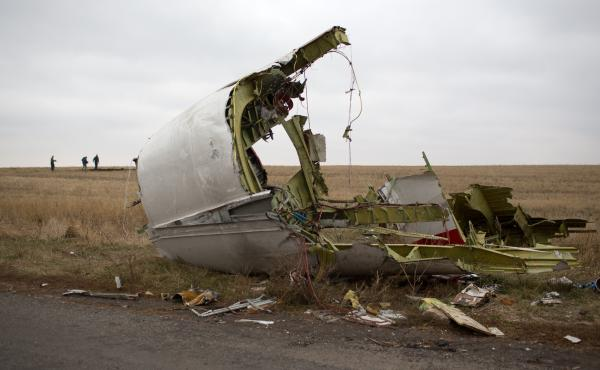 Journalists walk near parts of Malaysia Airlines flight MH17 near the Grabove village in eastern Ukraine on Nov. 11, 2014.